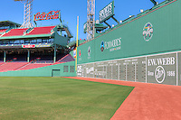 The Green Monster, the famed left field wall, towers over the field in iconic Fenway Park in Boston, Massachusetts.  Also shown is the left field corner and grandstands including the Coca-Cola Corner Pavilion.  Fenway is the oldest ballpark in Major League Baseball, dating from 1912.