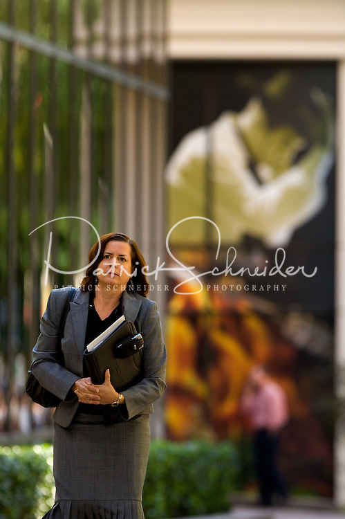 A female business professional in a suit walks down the street in uptown Charlotte, NC.