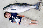Thirty-eight-pound Brendan Mills meets 42-pound striped bass after a successful day of fishing just off the beach in Asbrury Park Saturday. Experts say this season's striped bass run along the Jersey Shore is one of the best in decades. (5/21/2010)