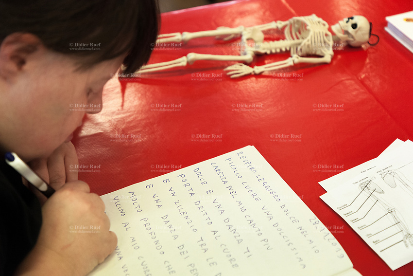 Switzerland. Canton Ticino. Locarno. Fauni Theater.  MOPS_DanceSyndrome is an independent Swiss artistic, cultural and social organisation operating in the field of contemporary dance and disability. It is composed only of Down dancers. Amedea Aloisi writes poetry in her notebook. A human plastic skeleton is laid on the table. Down syndrome (DS or DNS), also known as trisomy 21, is a genetic disorder caused by the presence of all or part of a third copy of chromosome 21 It is usually associated with physical growth delays, mild to moderate intellectual disability, and characteristic facial features. 29.11.2019 © 2019 Didier Ruef