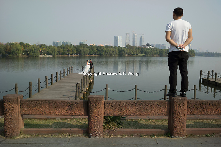 Huanggang, Hebei province, China - A couple has their wedding photo taken as a passers-by looks on at the Yiai Park which was built to commemorate famous Song dynasty poet and politician Su Dongpo, October 2014.