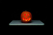Schenectady, NY. Spooky, lit and glowing jack-o-lantern carved from pumpkin on table in a dark room appears to be suspended in space. ID: AK-ICP. © Ellen B. Senisi
