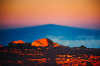 Mauna Kea, with rocks lit by sunset in the foreground, Big Island.