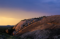 Sunset with storm clouds, Enchanted Rock State Natural Area, Texas.  Heavy clouds had not made me optimistic for sunset, but a small clearing on the horizon allowed the sun's beams to shine in for a short while.  On the horizon is Bullhead Mountain.