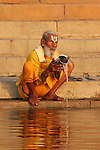 A man pours water into the holy Ganges River while saying his prayers in the early morning light.