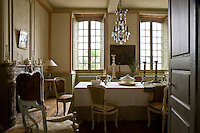A collection of Louis XV provencale chairs in the dining room surrounds a long table draped in a linen cloth beneath an 18th century Italian chandelier
