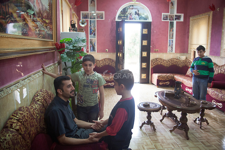 31/10/14. Alqosh, Iraq. father Yousif (left sitting), the manager of the orphanage, welcomes Milad (centre) and Wassam (second left) back to Alqosh. He asks what they did during their holiday.