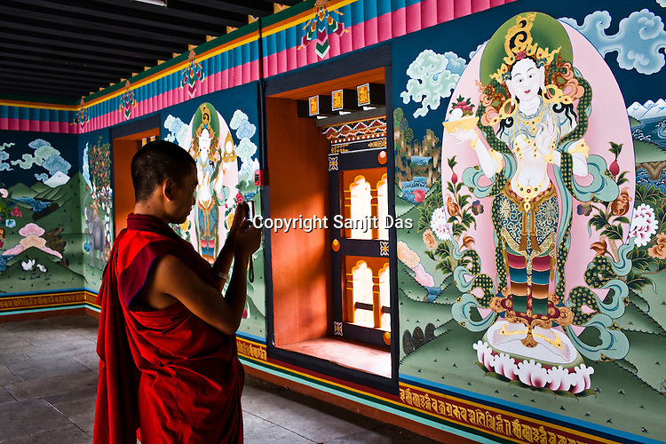 A Buddhist monk uses his mobile to take a photo of the painting of the earth deity at the Tashichhodzong (fortress of auspicious religion) in the capital city Thimphu, Bhutan. Photo: Sanjit Das/Panos
