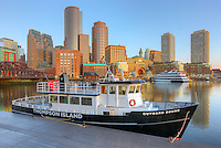 The Outward Bound Thompson Island Ferry sits moored in front of the skyline at sunrise in Boston, Massachusetts.