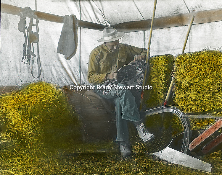 Jerome ID:  Homesteader repairing equipment in the temporary tent next to the farmhouse.  Brady Stewart and three friends went to Idaho on a lark from 1909 thru early 1912.  As part of the Mondell Homestead Act, they received a grant of 160 acres north of the Snake River.  Brady Stewart photographed the adventures of farming along with the spectacular landscapes. To give family and friends a better feel for the adventure, he hand-color black and white negatives into full-color 3x4 lantern slides.  The Process:  He contacted a negative with another negative to create a positive slide.  He then selected a fine brush and colors and meticulously created full-color slides.