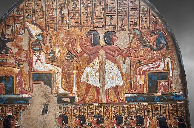 "Ancient Egyptian stele of scraftsman Minhotep in adoration of Osiris, limestone, New Kingdom, 18th Dynasty, (1336-1292 BC), Deir el-Medina, Drovetti cat 1619. Egyptian Museum, Turin. Grey background.<br /> <br /> The stele is dedicated to Osiris, Anubis and Hathor ""Mistress of the World""."