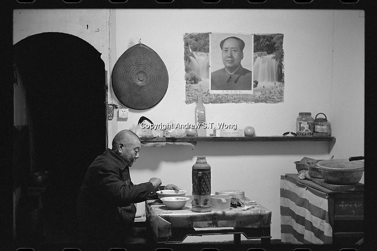 Changshan County, Quzhou City, Zhejiang Province - A man has dinner in front of a portrait of Chinese leader Mo Zedong, December 2020. Changshan County is located along the Qiantang River.