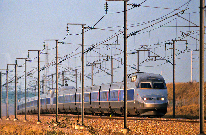 France. TGV, train a grande vitesse, running through cable supports and pylons.  Double train.