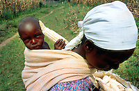 Kenya. Rift Valley Province. Matisi. A woman carries her child on her back. The little girl holds in her hand a cob of corn. © 2004 Didier Ruef