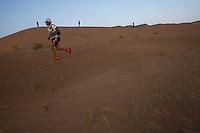 The Marathon des Sables is a 6-day endurance race of 243 km equivalant to 5 1/2 marathons. It plays out in the Sahara Desert, southern Morocco, up and down sand dunes, along dried lakes and riverbeds, past ruins, always under the baking sun. Competitors at the Marathon des Sables expierence mid-day temperatures of up to 120°F. They are running or walking on even rocky, stony ground as well as 15-20% of the distance being in sand dunes. In addition to that, competitors have to carry everything they will need for the duration of the race on their backs in a rucksack. Water is rationed and handed out at each checkpoint. It is the hardest footrace on earth...Der Marathon des Sables in der marrokanischen Sahara gilt als der wohl härteste und bekannteste Wüstelauf der Welt. Ein Ultralauf über 243 Kilometer, der in 6 Etappen zwischen 27 und 82 Kilometer in 7 Tagen gelaufen wird. Die längste Etappe geht bis spät in die Nacht hinein. Die Läufer tragen ihre Ausrüstung und Verpflegung für das ganze Rennen im Rucksack. Lediglich Wasser (9 Liter pro Tag) gibt es an den Checkpoints. Die Teilnehmer laufen über Sanddünen, steiniges Gelände und steile Berganstiege. Die Hitze kann bis zu 50 Grad Celsius betragen. , Aziz El Akad