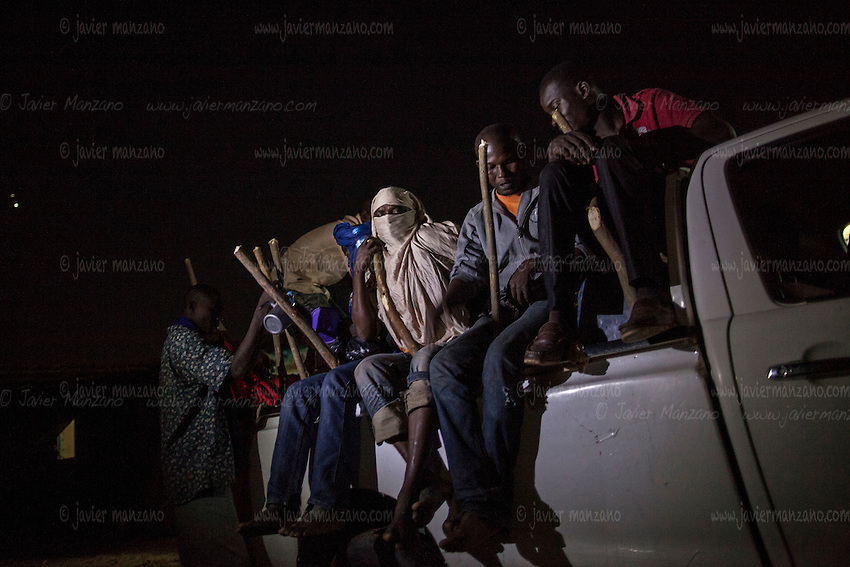 AGADEZ, NIGER — <br /> Migrants take their positions on the back of a Toyota pick-up truck loaded with water, provisions and fuel. Wooden stakes were lodged in-between water bottles, back-packs and fuel tanks in order to provide the passengers - a  total of 25 migrants - with something to hold on to for the long journey to Libya.