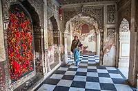 India, Dehradun. Indian Woman inside the Durbar Shri Guru Ram Rai Ji Maharaj, a Sikh temple built in 1707.  Visitors tie bits of red cloth to the window latticework as a symbol of prayers offered.