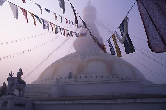 NEPAL, KATHMANDU, BOUDHNATH, TIBETAN STUPA (TEMPLE) IN FOG, PRAYER FLAGS, STATUE