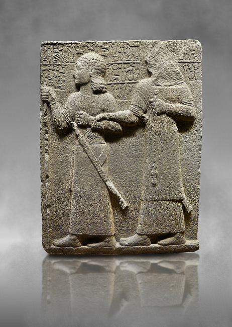 """Hittite monumental relief sculpted orthostat stone panel of Royal Buttress. Basalt, Karkamıs, (Kargamıs), Carchemish (Karkemish), 900-700 B.C. Anatolian Civilisations Museum, Ankara, Turkey.<br /> <br /> King Araras holds his son Kamanis from the wrist. King carries a sceptre in his hand and a sword at his waist while the prince leans on a stick and carries a sword on his shoulder. <br /> <br /> Hieroglyphs reads; """"This is Kamanis and his siblings.) held his hand and despite the fact that he is a child, I located him on the temple. This is Yariris' image"""".  <br /> <br /> Against a grey art background."""