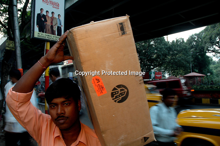 An Indian man carries a curtain with a logo of Cisco in Kolkata, India  6/13/2007  Arindam Mukherjee