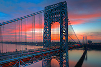 Morning rush hour traffic creates streaks of light on the George Washington Bridge as commuters cross the Hudson River between Fort Lee, New Jersey and Fort Washington, New York under a colorful sky just before sunrise on a spring morning.