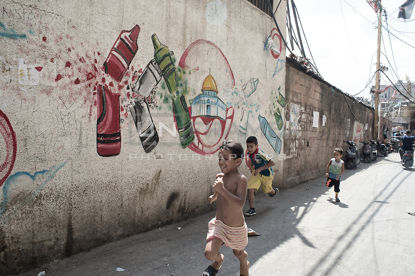 Group of kids running in the streets in front of the school for Palestinian children in Shatila camp run by the UN which has recently been shut for lack of funds. Beirut, Lebanon. August 2015