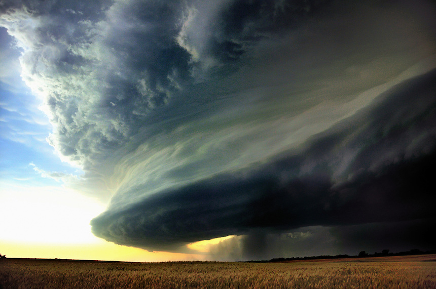 A large supercell thunderstorm approaches a field of golden wheat southwest of Salina Kansas in June. This storm produced a damaging tornado in the southern portions of Salina an hour after this image was taken.