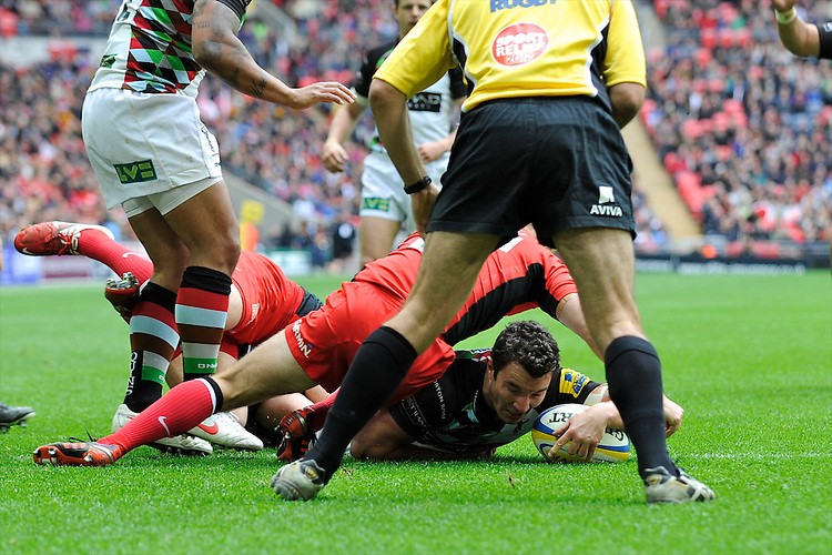 George Lowe of Harlequins breaks through the tackles of Alex Goode and Charlie Hodgson of Saracens to score a try during the Aviva Premiership match between Saracens and Harlequins at Wembley Stadium on Saturday 31st March 2012 (Photo by Rob Munro)