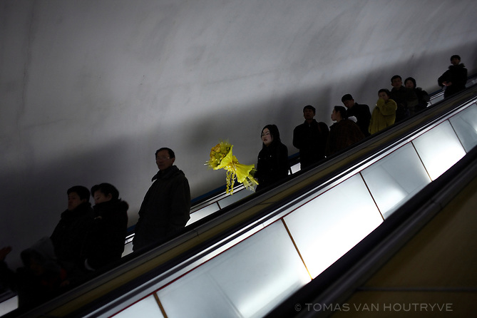 A Korean woman carries a bouquet of yellow flowers down the escalator into the Pyongyang metro subway, North Korea (DPRK) on 24 February 2008.