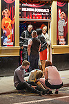 © Joel Goodman - 07973 332324 . Manchester , UK . 05/04/2015 . A man and a woman watch over a woman who is slumped forward on the edge of a pavement on Sackville Street , in Manchester City Centre . Revellers on a Saturday night out during the Easter Bank Holiday weekend . Photo credit : Joel Goodman