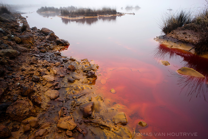 Toxic water which is tinted red from contamination by mine tailings is seen from the shore of the Quilacocha lagoon, near Cerro de Pasco, Peru.