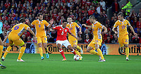 Neil Taylor of Wales (C)crosses the ball to the Moldova box while being marked by five Moldova players during the 2018 FIFA World Cup Qualifier between Wales and Moldova at the Cardiff City Stadium on September 5, 2016 in Cardiff, Wales.