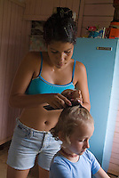 Teenage girl styling a young girl's hair at home in Vinales, Pinar del Rio Province, Cuba.