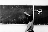 Hungary. Baranya County. Pécs. Gandhi High School.  Mathematics class. A boy cleans the blackboard. The purpose of the middle school / high school is to provide a school-leaving exam (A-level), also to improve the prospects of Romani children in Hungary and to help preserving the Romani culture. The Romani people, also known as the Roma, are an Indo-Aryan people group, traditionally nomadic itinerants living mostly in Europe. The Romani people are widely known in English by the exonym Gypsies (or Gipsies), which is considered by many Romani people to be pejorative due to its connotations of illegality and irregularity as well as its historical use as a racial slur. In many other languages, they are called Roms (Rroms), Tziganes,Tsiganes, Gitans, Bohémiens, Manouches, Romanichels, gitano, zingaro and cigano. The Gandhi High School in Pécs, was founded with donations given by several individuals from the private sector mostly those of Romani origin Romani and with further donations from other organizations. In 1992, the Gandhi High School became  the first Romani high school, that has been actively operating since 1994. It was named after the Indian Mahatma Gandhi, to emphasize the Indian origin of all Romani groups. The school consists of 6 classrooms where about 250 male and female pupils study, mostly between the ages of 14 to 18. The first group of students beginning in 1994 took their school-leaving exam (A-level) in 2000 and out of 18 pupils, 16 have applied to universities, while 7 out of the 18 students gained entry to their desired universities. Pécs is the fifth largest city of Hungary. It is the administrative and economic centre of Baranya County. 9.05.95  © 1995 Didier Ruef
