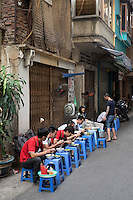 People eating soup, Street scene in Hanoi, Vietnam