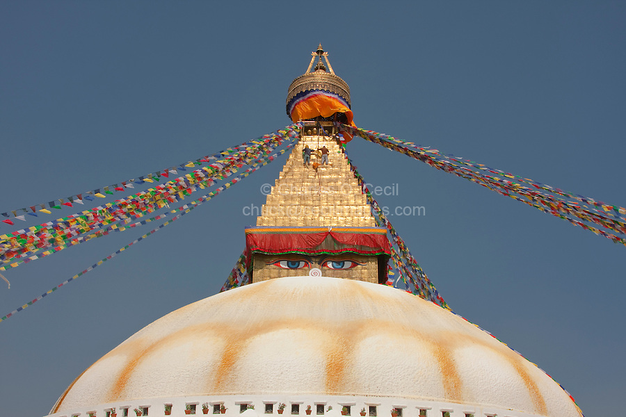 Bodhnath, Nepal.  The All-Seeing Eyes of the Buddha Gaze out from above the Stupa of Bodhnath, a center of Tibetan Buddhism, near Kathmandu.  Workers clean the 13 tapering levels above the dome, representing the 13 stages of perfection leading to nirvana.  Saffron stain decorates the dome.