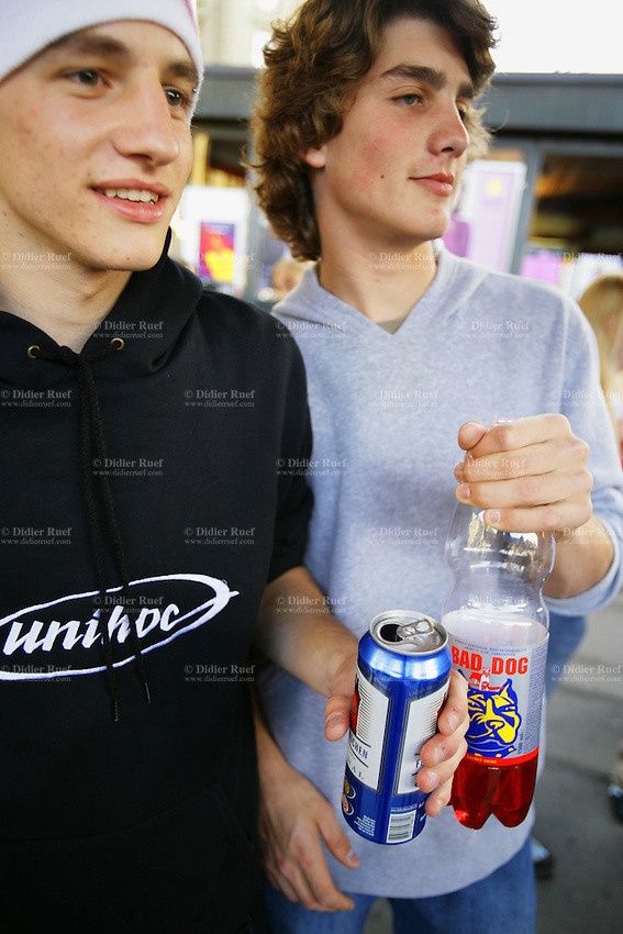 Switzerland. Canton Bern. Bern. Two young men with alcohol drinks in their hands. One holds a Feldschlossen beer in an aluminium can, the other a plastic bootle of Bad Dog energy drink mixed with a strong alcohol. © 2006 Didier Ruef