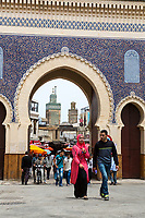 Fes, Morocco.  Bab Boujeloud, Entrance to Fes El-Bali, the Old City.  Woman in Modern Traditional Dress, Man in Levis and Western Attire.
