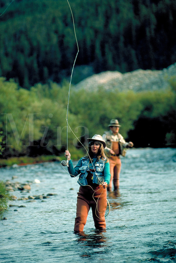 Woman and man fly fishing in the backcountry of the Colorado Rocky Mountains. Colorado.