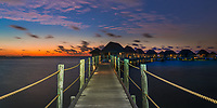 Colorful twilight on a light painted pier and luxury overwater bungalows, in Tikehau atoll Tuamotus Archipelago, French Polynesia, South Pacific Ocean