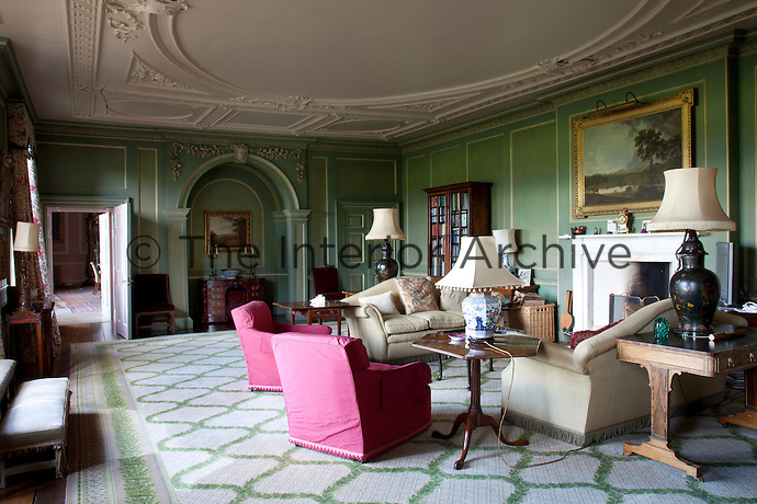 A green, panelled living room furnished with comfortable armchairs and sofas