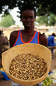 The Gambia. Woman holding a bowl full of peanuts.
