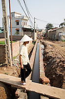 Vietnam. Ha Tay province. Dai Tu. A woman, wearing a traditional vietnamese hat, walks on a board over the new sewage system. Through the construction of a main drainage and the building of sewerage as a combined system, collecting both rainwater and domestic waste water, the implementation of a flexible decentralized community sanitation project in a context of low infrastructure investment and in a peri-urban case study, such as Dai Tu, will be a major sucesss. It offers importants benefits as an alternative to centralized systems, namely in terms of health improvements and by the possibility of dealing with wastewater locally, through households and decentralized municipal structures.  Dai Tu is a typical hamlet (village) and is part of the Kim Chung commune located 15 km west of Hanoi. The peri-urban location is under increasing pressure of urbanization. 06.04.09  © 2009 Didier Ruef
