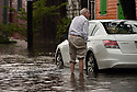 Blue Flettrich races to move his car after rains flooded streets in the historic Faubourg Marigny because city pumps were overwhelmed, New Orleans, Sat., Aug. 5, 2017. (Photo by Cheryl Gerber)