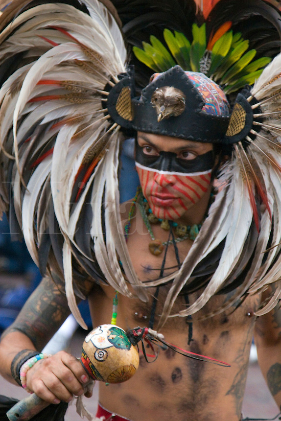 An AZTEC DANCER dressed as a WARRIOR with headdress, rattle and shield during the CERVANTINO FESTIVAL  - GUANAJUATO, MEXICO