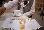 Essaouira, Morocco. Pouring mint tea into a decorated glass from a silver teapot.