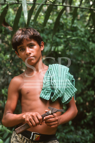 Acre State, Brazil; young rubber tapper in the forest holding his rubber tapping tool.