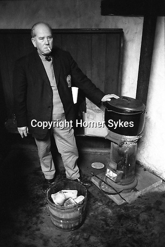 Wassailing the Apple Tree. Carhampton Somerset. England . 1972. The toast in the Wassailing bucket is soaked in mulled cider, made from a secret receipt and then placed in the apple tree to ensure a good crop for the following year.<br /> <br /> The original use of the word 'wassail' was as a greeting when drinking the health of a person, and derives from the Anglo-Saxon<br /> wes hal, or 'Be in good health'. Later it came to describe a custom observed on New Year's Eve and Twelfth Night of drinking healths from a wassail-bowl. Connected with this appears to have been the practice of wassailing cattle or fruit-trees to encourage<br /> them to thrive, a custom performed either right at the end of an old year or at the beginning of a new.  The people of Carhampton carry it out on the date of the old<br /> Twelfth Night (17 January) in an apple orchard behind the Butchers' Arms Inn. The wassailers gather round one of the largest apple trees to address it, sing the wassailing song, and fire<br /> guns into the tree to frighten off the evil spirits. After warm cider with toast in it has been passed around, the health of the tree is<br /> drunk, and toast put in the branches, supposedly for the birds who, it is hoped, will keep a watchful and benevolent eye on the<br /> tree for the following year.<br /> <br /> In 1972 the wassailing song went:<br /> Old apple tree we wassail thee and hoping thou wilt bear,<br /> For the Lord doth know where we shall be till apples come another year.<br /> To bear well and to bloom well so merry let us be,<br /> Let every man take off his hat and shout to the old apple tree.<br /> Old apple tree we wassail thee and hoping thou wilt bear<br /> Hatfuls capfuls three bushel barfuls,<br /> And a little heap under the stairs.<br /> Hip! Hip! Hooray!