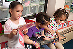Education preschool 4-5 year olds group of three girls pretend play one singing the others providing the music