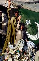 Islamabad / Pakistan.Outdoor market. Young people with national flag..Photo Livio Senigalliesi